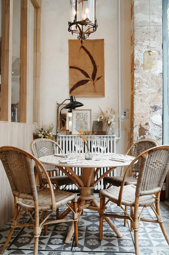 L'Avant-Poste restaurant's bohemian farmhouse style interiors with bamboo chairs.