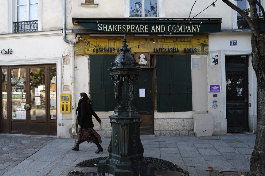 "A woman walks by the closed English and American literature Shakespeare and Co. bookstore in Paris, France, Thursday, Nov. 05, 2020. Iconic Parisian bookshop Shakespeare and Co. has launched a support appeal to its readers after its owners say that coronavirus-linked losses, and a crippling months-long lockdown, have left the future of the veritable institution in doubt. ""We've been minus 80 percent since the first confinement in March, so at this point we've used all our savings,"" Sylvia Whitman, daughter of the shop's co-founder George Whitman, told the Associated Press. (AP Photo/Francois Mori)"