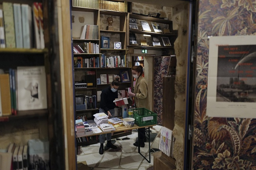 "Employees sort books in the English and American literature Shakespeare and Co. bookstore, in Paris, France, Thursday, Nov. 05, 2020. Iconic Parisian bookshop Shakespeare and Co. has launched a support appeal to its readers after its owners say that coronavirus-linked losses, and a crippling months-long lockdown, have left the future of the veritable institution in doubt. ""We've been minus 80 percent since the first confinement in March, so at this point we've used all our savings,"" Sylvia Whitman, daughter of the shop's co-founder George Whitman, told the Associated Press. (AP Photo/Francois Mori)"